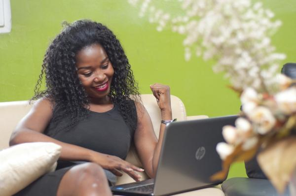 A lady sitting on a sofa with a laptop – front view smilling