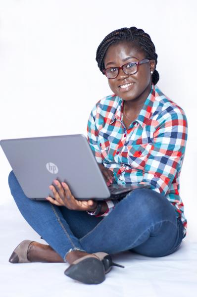 A Lady sitting on the floor and holding a laptop in her hands - smiling