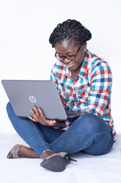 A Lady sitting on the floor and holding a laptop in her hands
