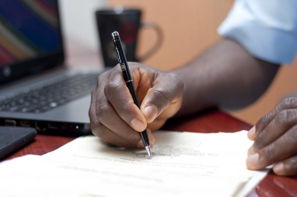 A man writing with a pen and paper - close view