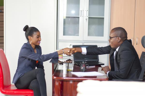 Business man and woman in an office having a hand shake - sealing a deal