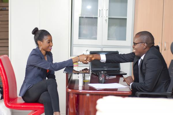 Business man and woman in an office having a hand shake - smiling
