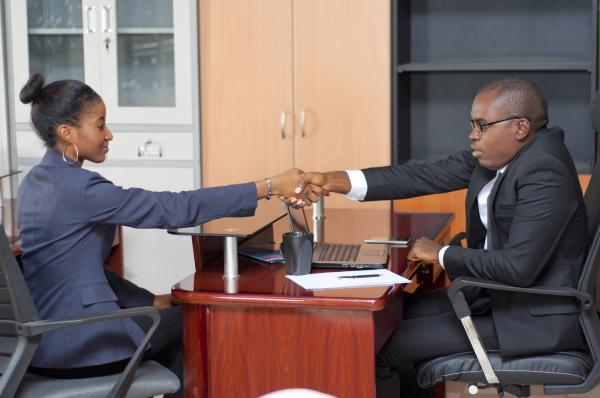 Business man and woman in an office having a hand shake
