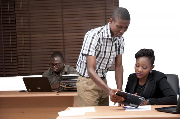 A guy sharing information with colleague from his I-pad
